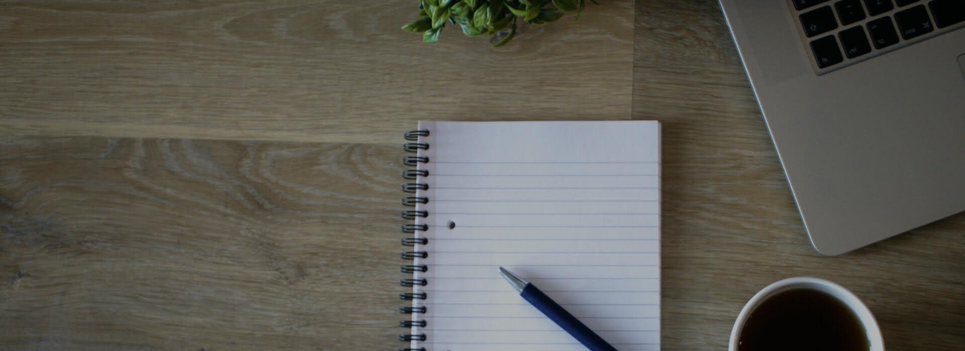 Home slider image - laptop, notepad, tea and plant on desk