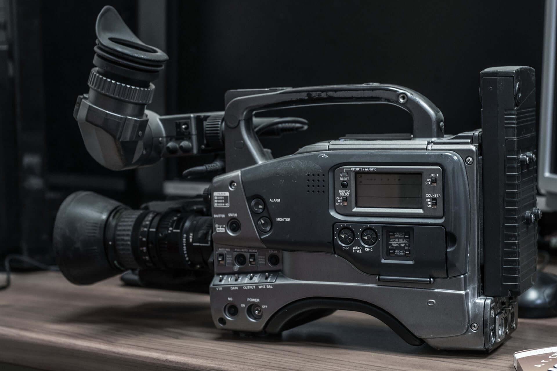 A black, vintage, VHS-based video recorder on a desk surface