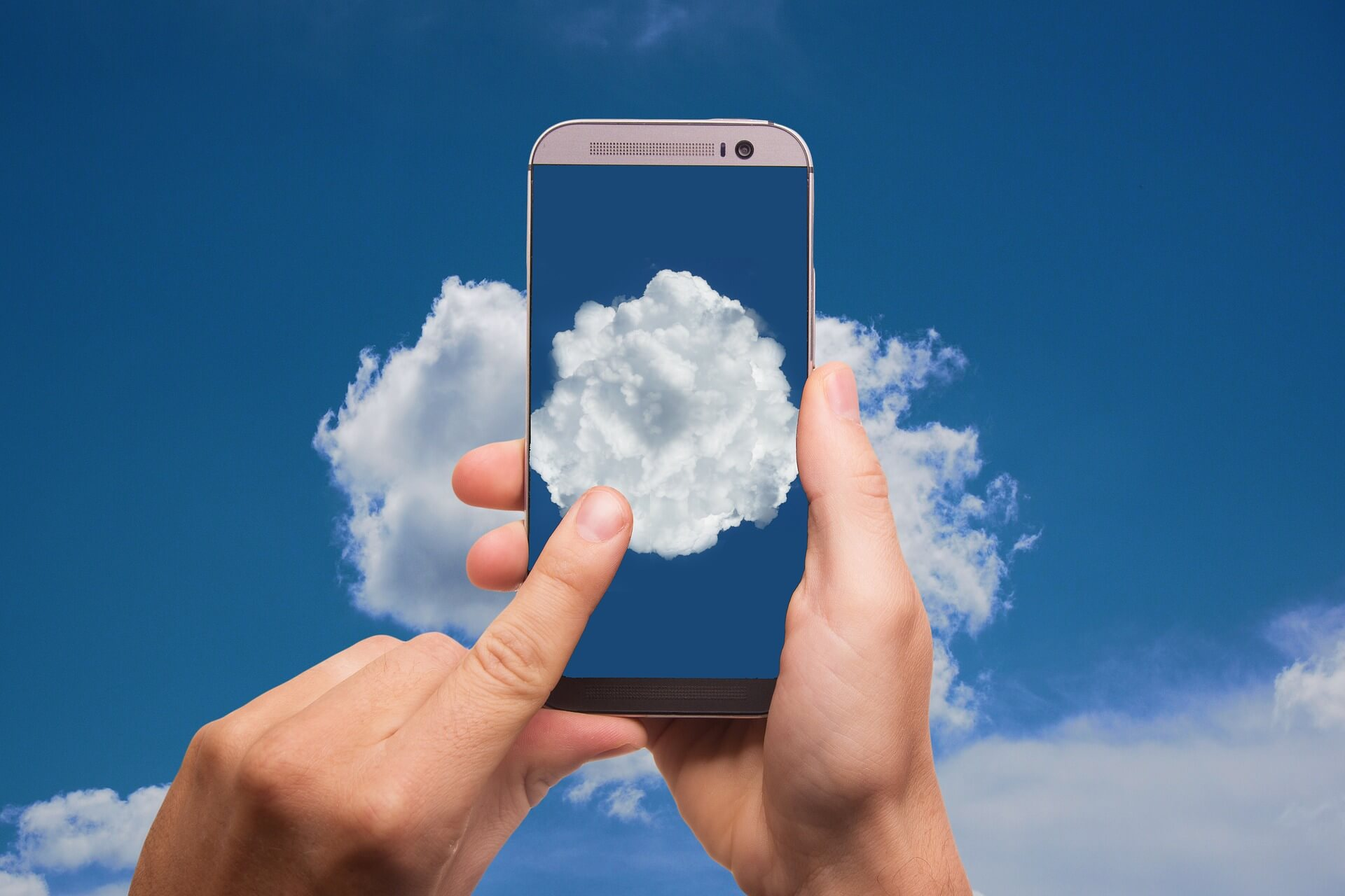 White clouds on blue sky, with a smartphone being held, showing the same thing
